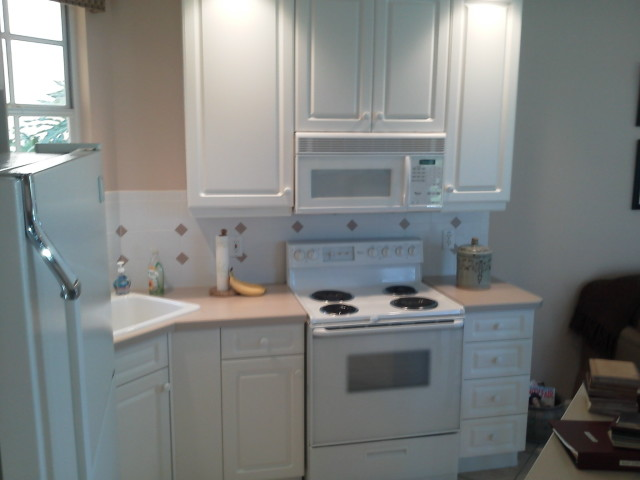 Before cabinet refacing, white cabinets, stove surround