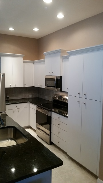 A before picture of plain white cabinets refaced by Kitchen Facelifts