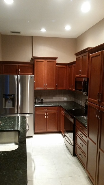 After pictures of what once were plain white cabinets but now are beautifully refaced with a rich wood style by Kitchen Facelifts.