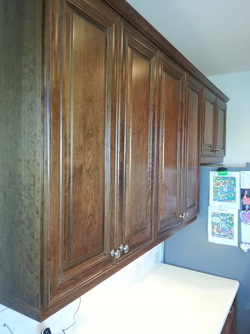 Above the counter cabinets refaced with a dark wood finish by Kitchen Facelifts in Southwest Florida