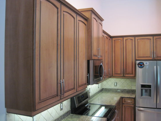 Kitchen Facelifts gave this kitchen warm wood tones to match the rest of the home's interior style
