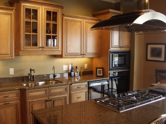 Cabinet refacing performed by Kitchen Facelifts. Warm maple tone cabinets add to the look of this gourmet kitchen remodel.