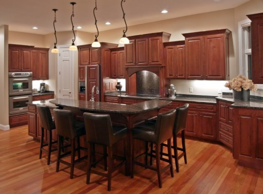 After cabinet refacing from Kitchen Facelifts, the dark wood on these cabinets complemented the interior style of the home.